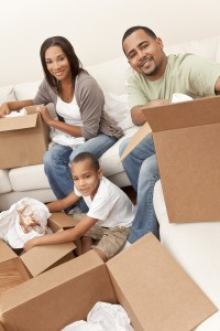 African American family, parents and son, unpacking boxes and moving into a new home, The adults are unpacking crockery and homeware, the child is unpacking a t