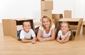 Woman with kids playing in their new home with cardboard boxes